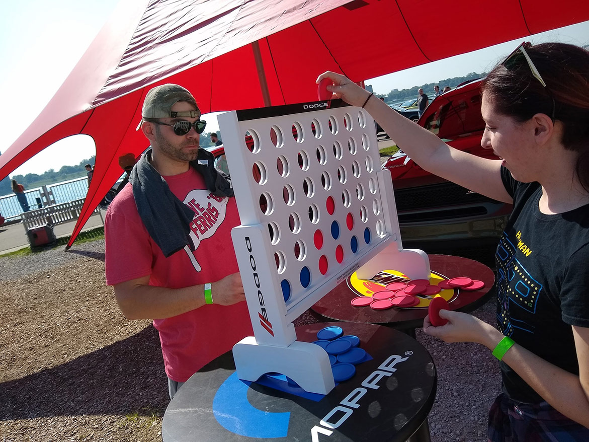 man and woman playing an oversized connect four game
