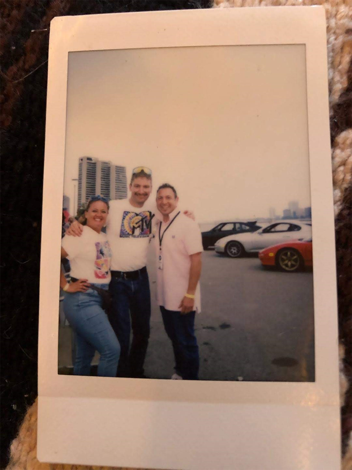 photo of a poloroid of two men and one woman