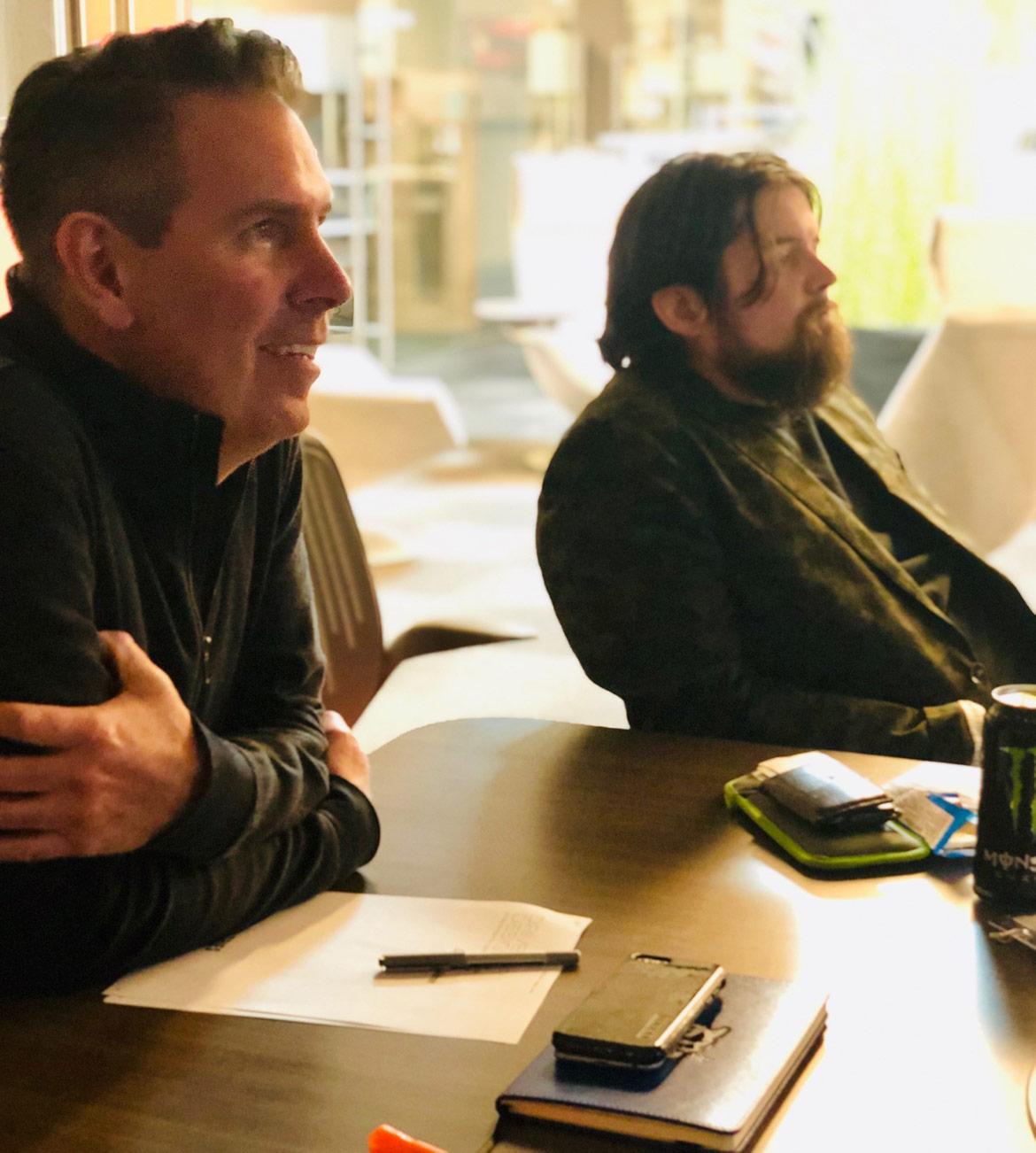 Two men watching presentations