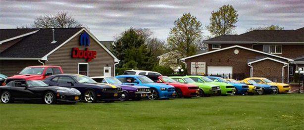 many dodge vehicles parked outside a mopar barn