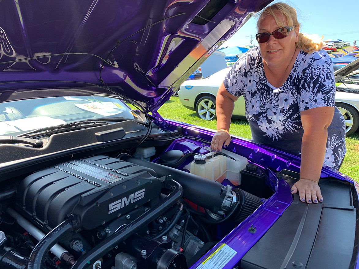 woman showing the engine of her dodge vehicle