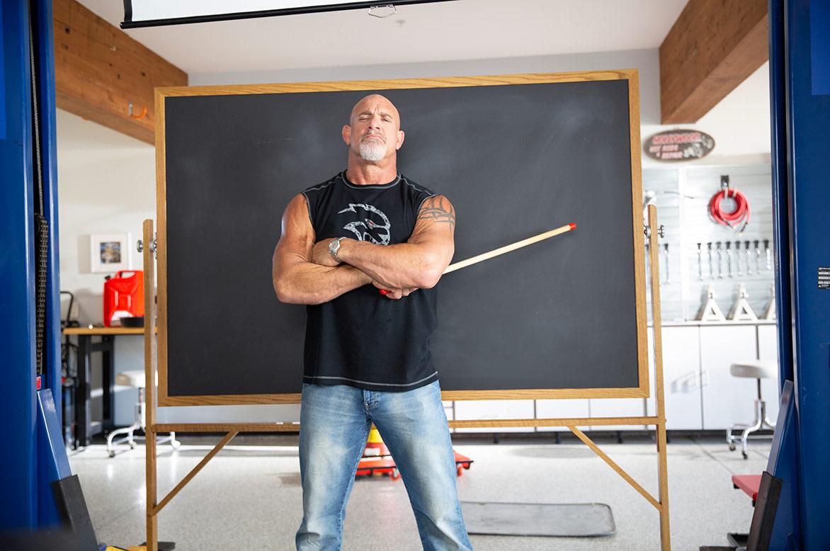 bill goldberg standing in front of a chalkboard
