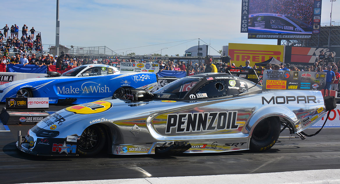 funny cars on the starting line of a drag strip