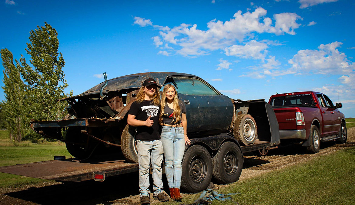olivia crosby and her husband standing with the decrepit plymouth vehicle on a trailer bed