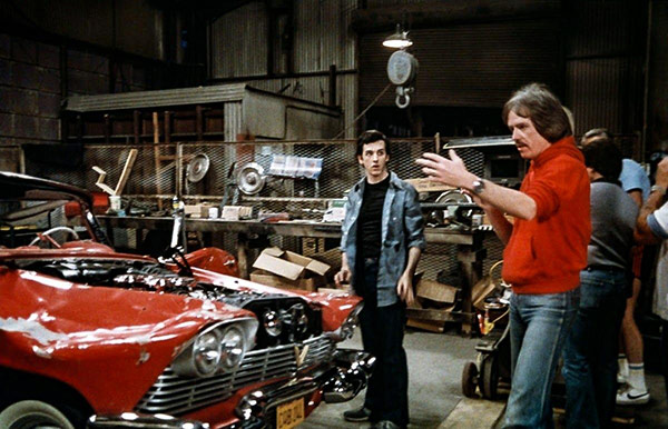 group of men in a garage with a vehicle