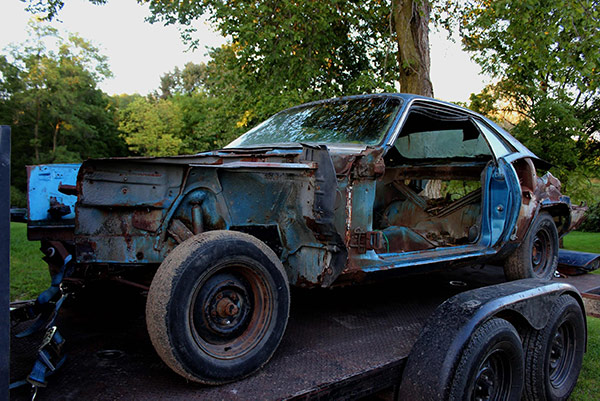 decrepit plymouth vehicle on a trailer bed