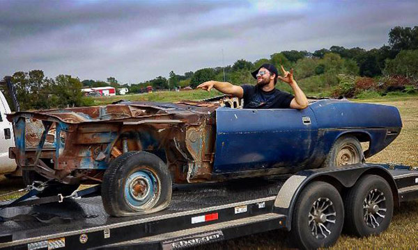 man sitting in decrepit plymouth vehicle