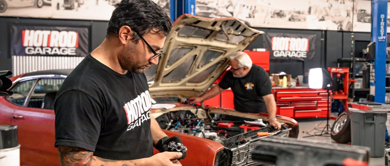 two men working on a car in their garage