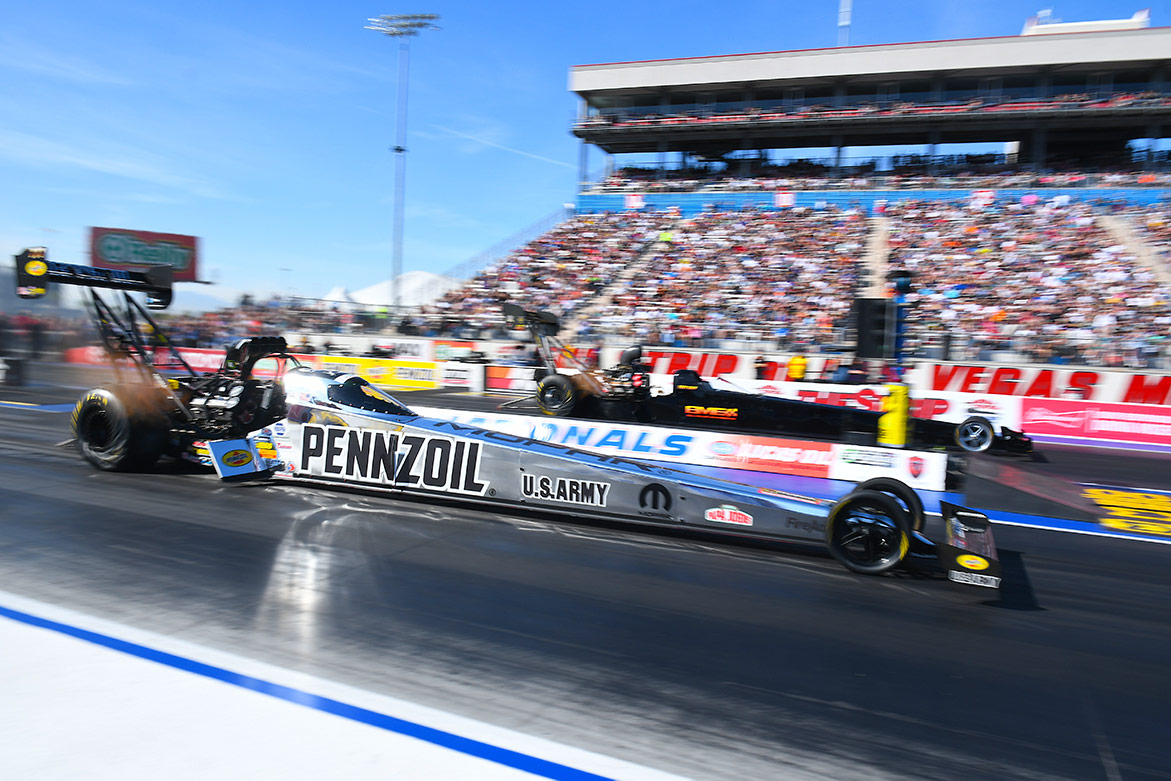 top fuel dragsters on the starting line of a drag strip
