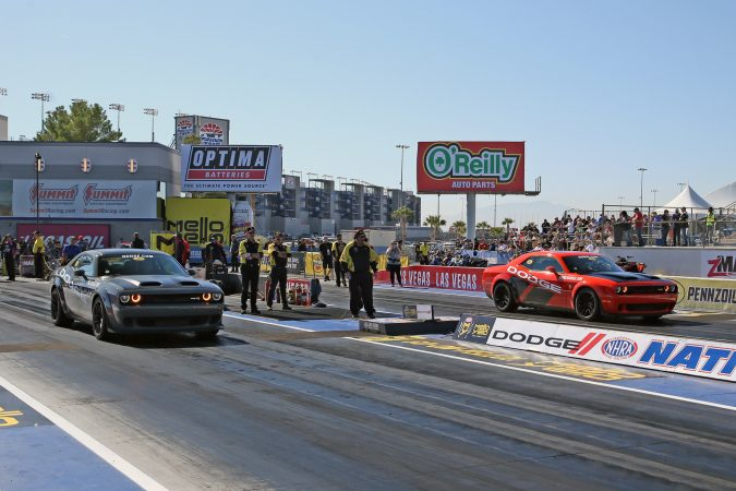 dodge challengers on the starting line of a drag strip