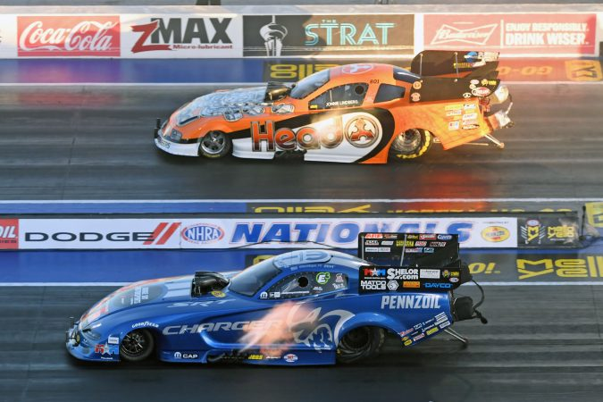 two funny cars on the starting line of a drag strip