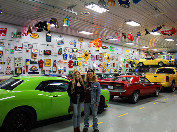 olivia crosby and luke crosby in a garage with several vehicles