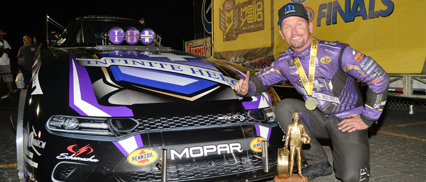 jack beckman with his funny car and wally trophy