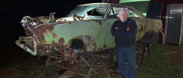 man standing next to old mopar