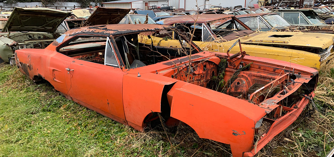 row of mopar vehicles in junkyard