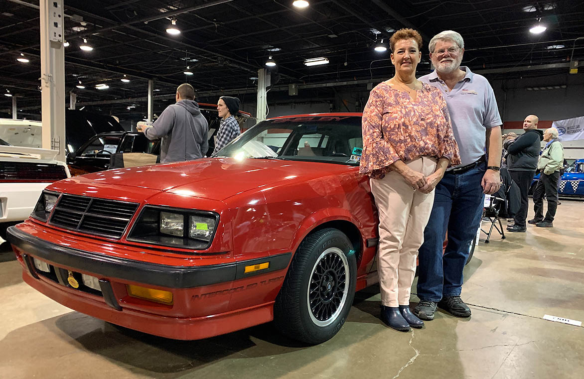 Man and woman standing next to Shelby Lancer