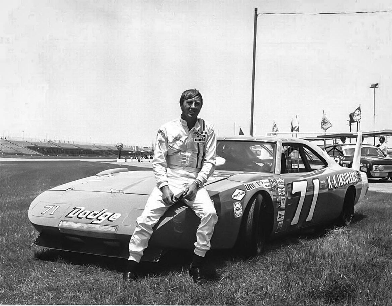 man sitting on the hood of a dodge racing vehicle