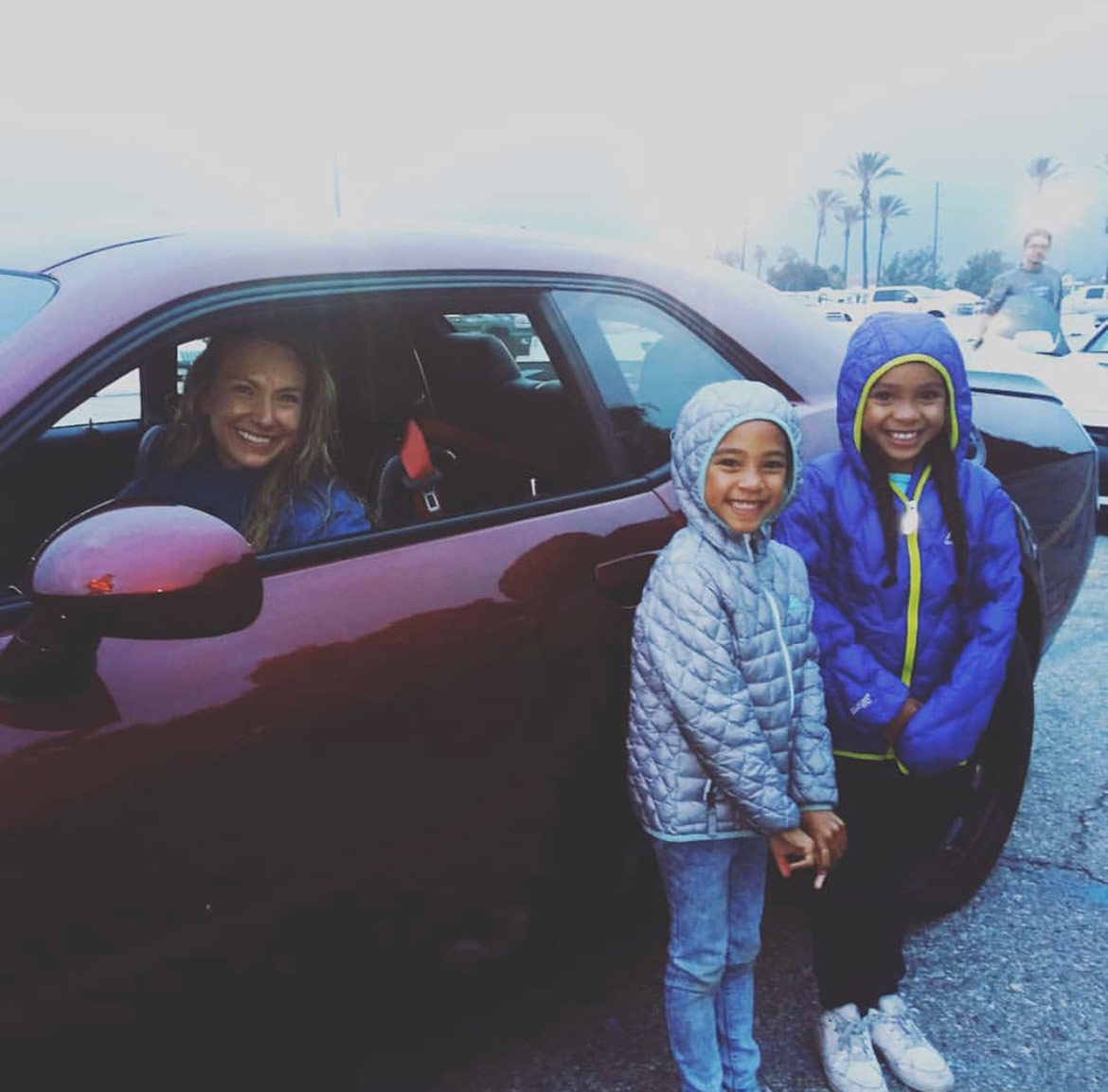 woman in a car and two little girls standing outside the car