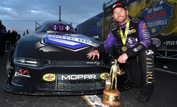 Jack Beckman kneeling in front of his Funny Car with the Wally trophy he won at NHRA Winternationals