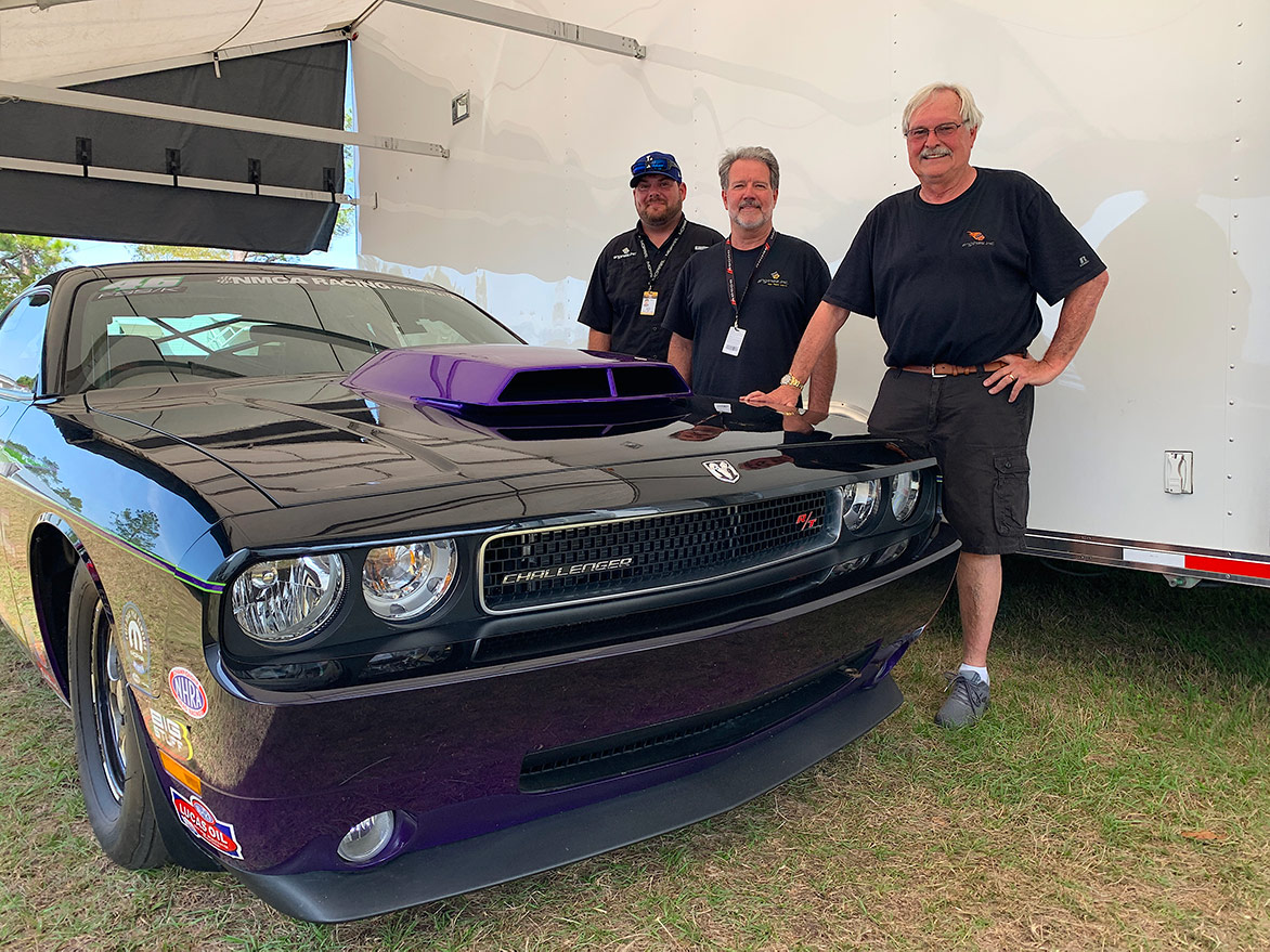 three men with a dodge challenger