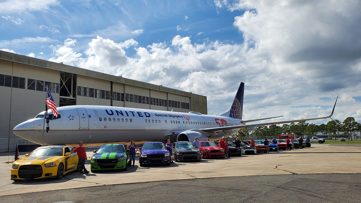 cars on display in front of a jet airplane