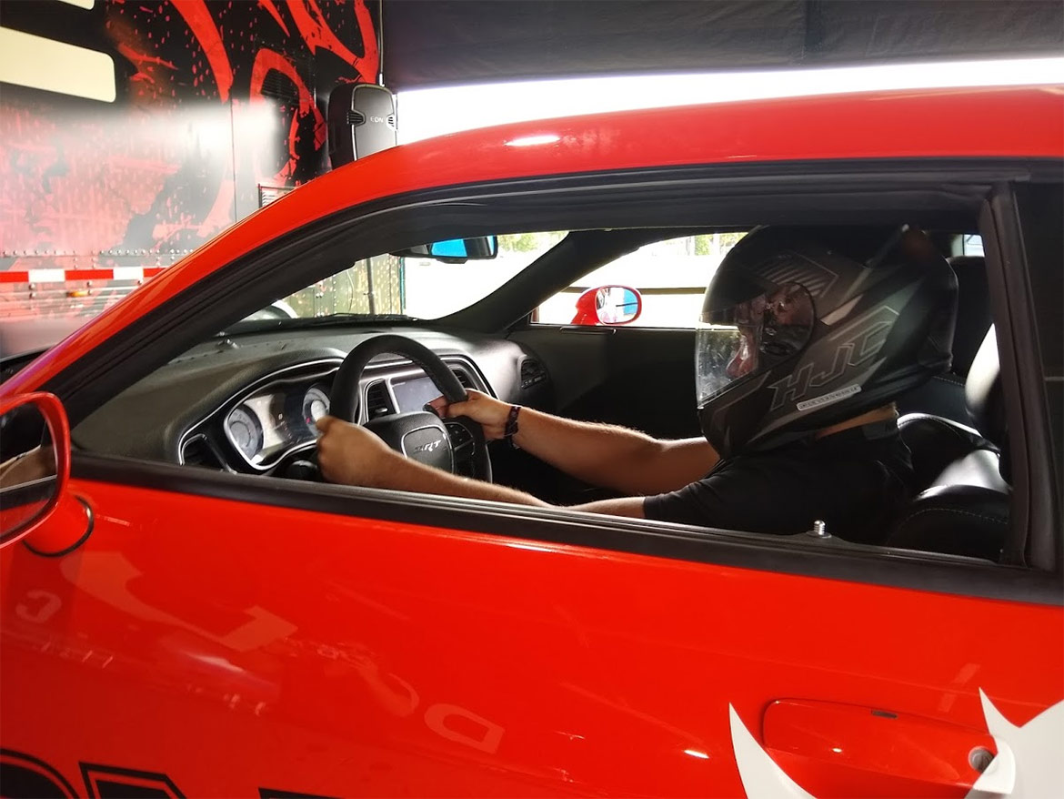Enthusiast wearing a helmet driving a dodge vehicle simulator