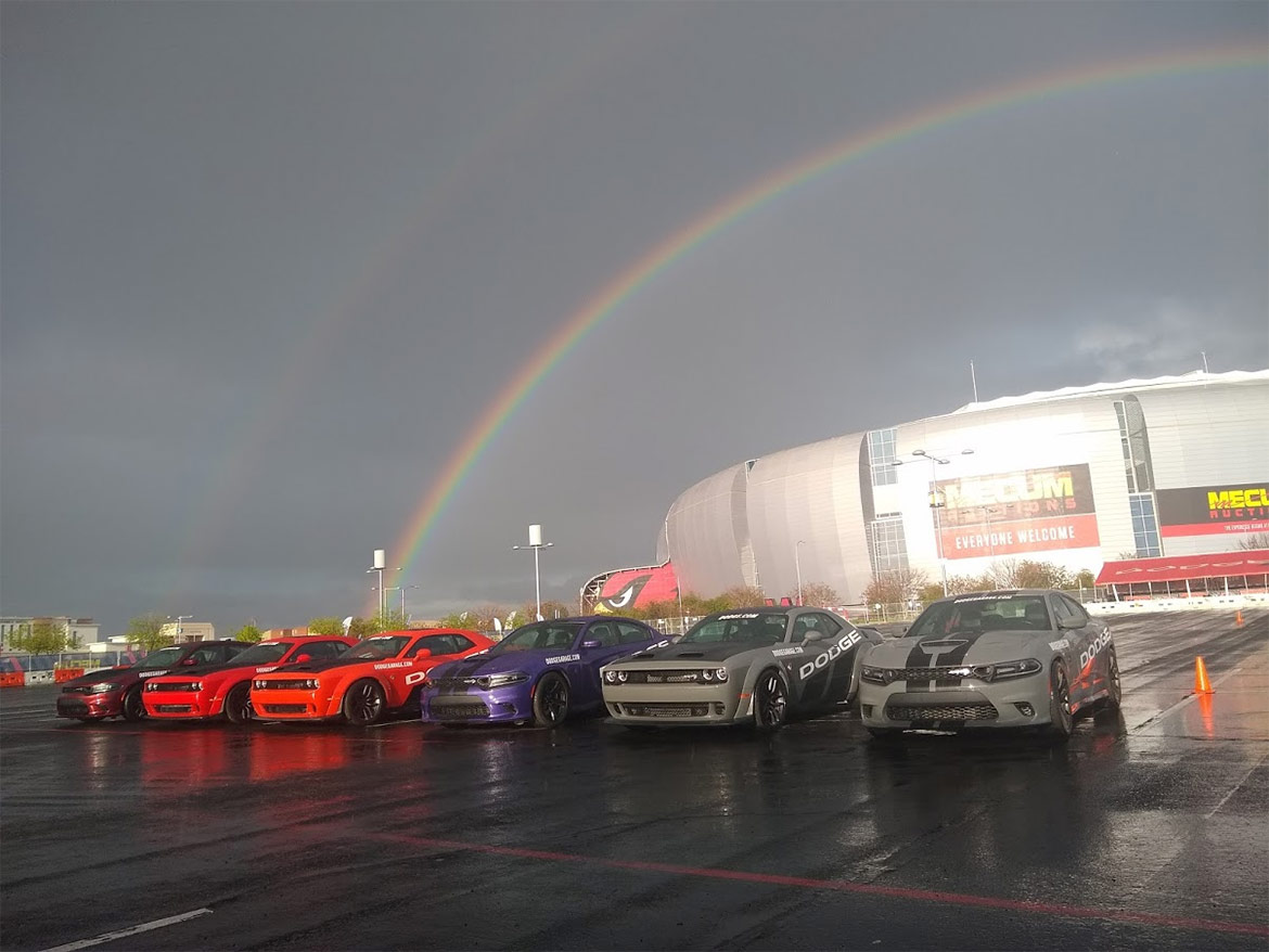Dodge vehicles lined up under a rainbow
