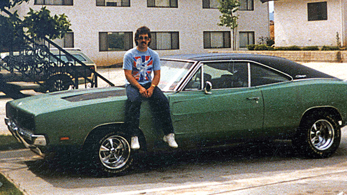 lee storz sitting on the hood of his dodge charger