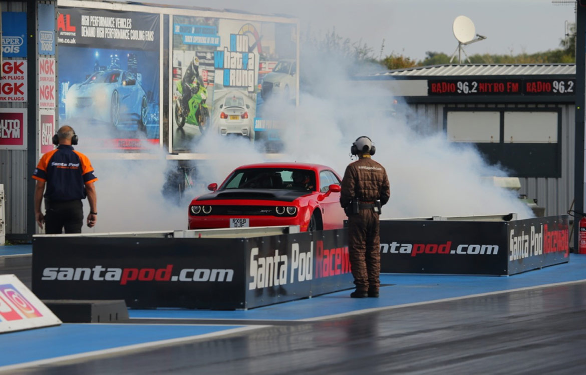 Dodge vehicle doing a burnout on the starting line of a drag strip