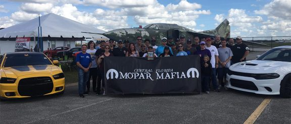 club members group picture with cars and a banner