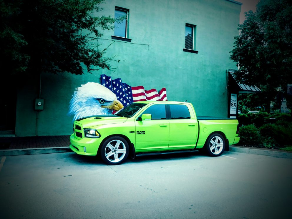 vehicle on display in front of bald eagle and American flag wall mural