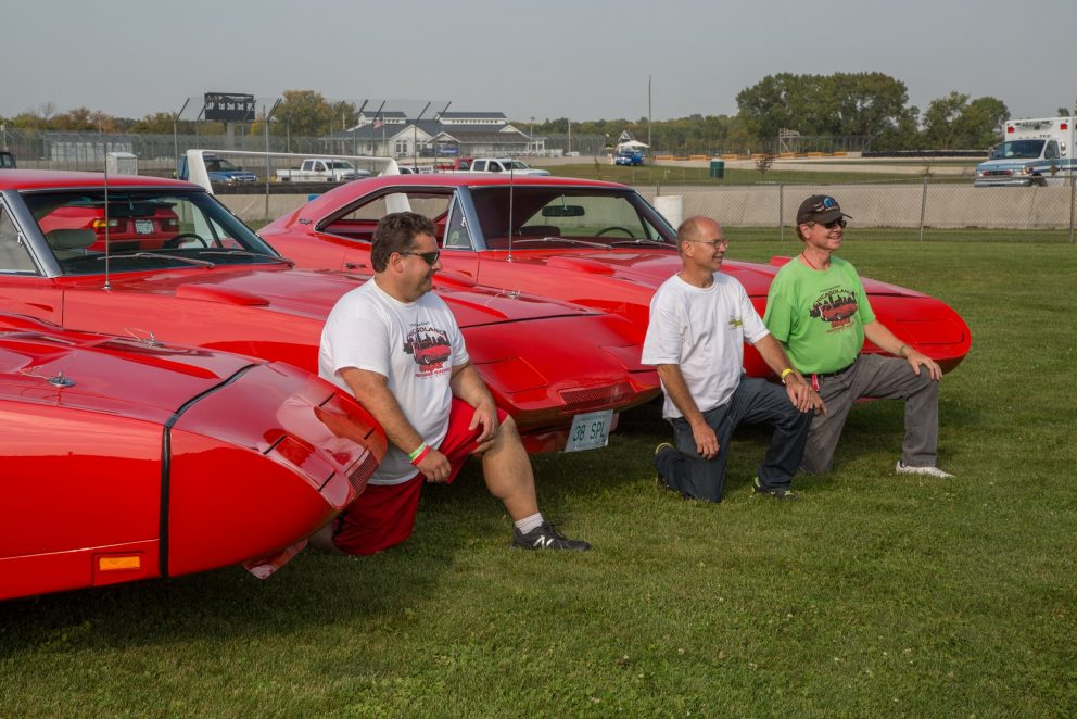 three men posing with vehicles