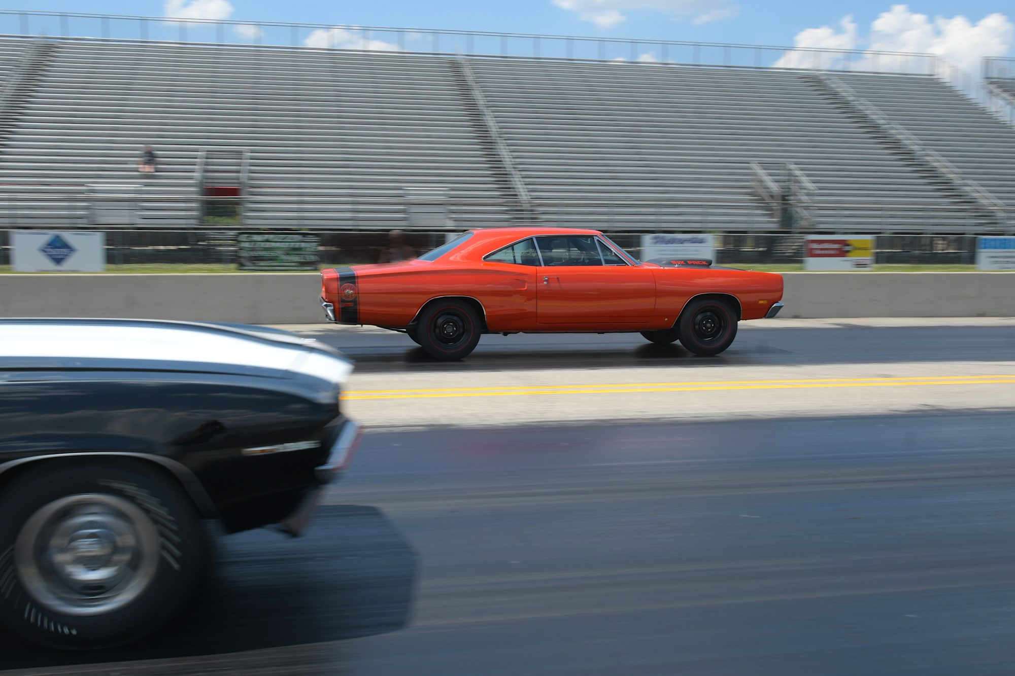 two vehicles racing on a drag strip