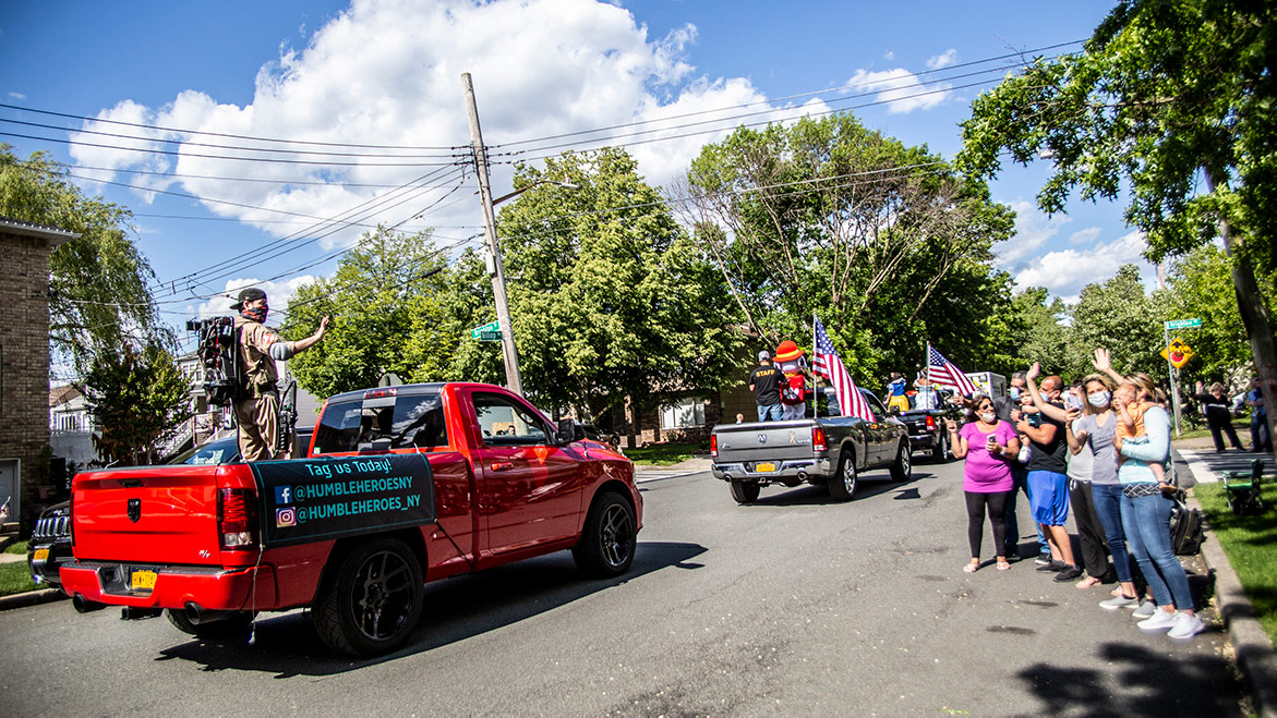 spectators waving at parade vehicles
