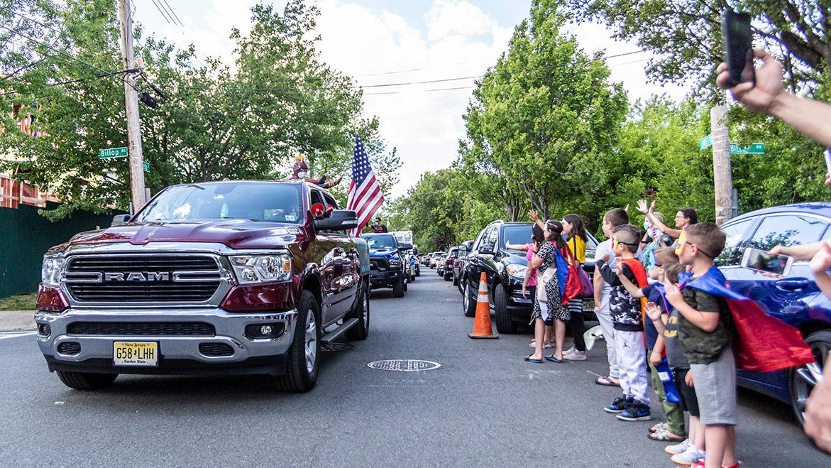 spectators waving at parade vehicles
