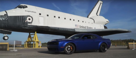 Dodge vehicle parked next to an airplane