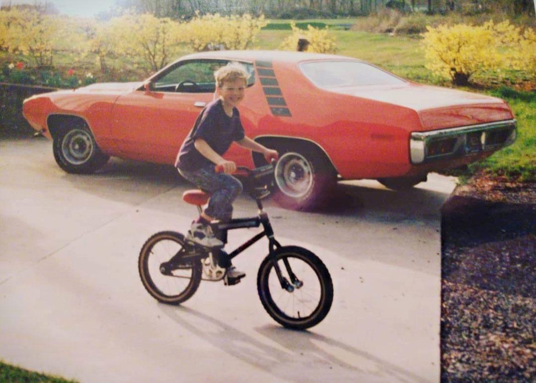 child riding a bike near a vehicle