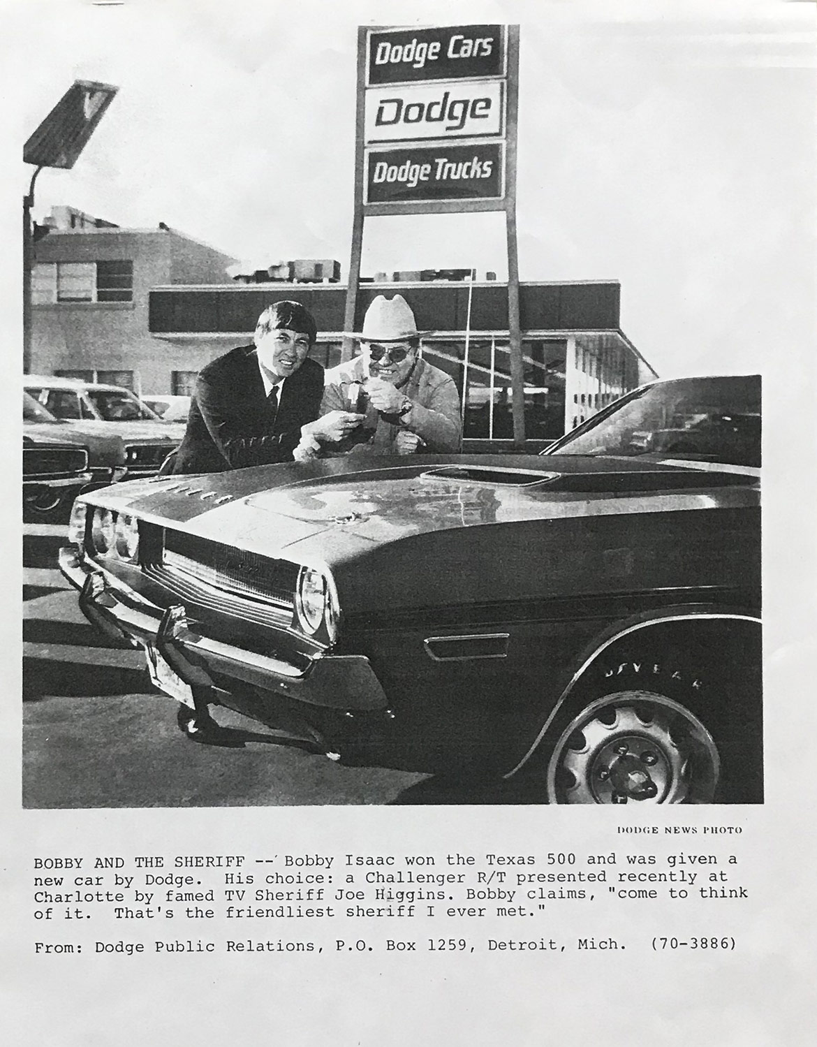 old picture of two men with a car at a dodge dealership