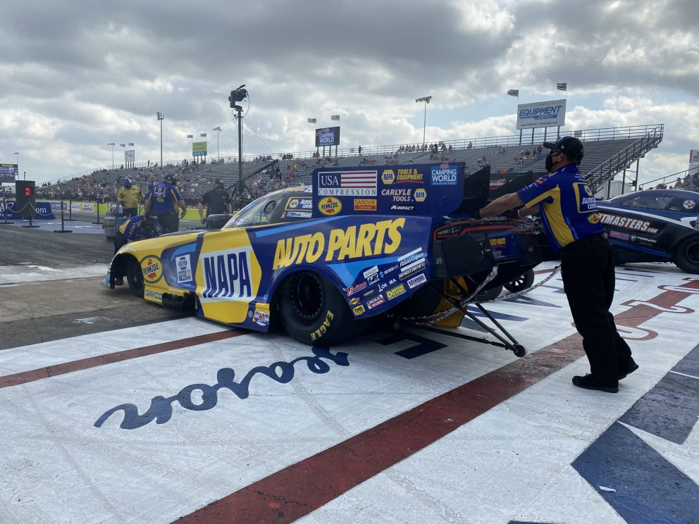 Ron Capps' team pushing his car to the start line
