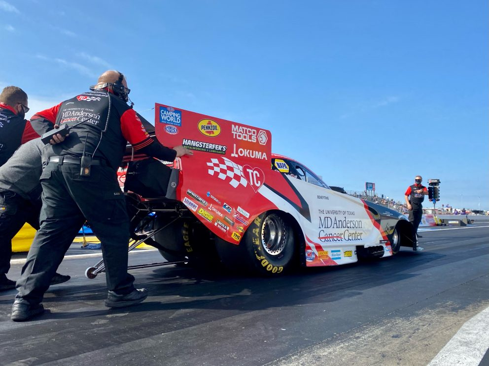Tommy Johnson Jr's crew pushing his funny car to the start line
