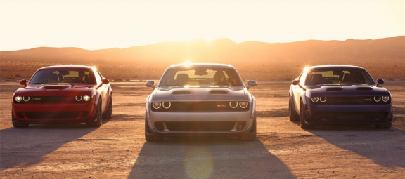 Three Dodge Challengers parked in front of a sunset