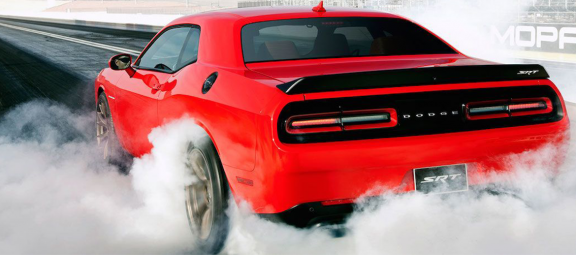 challenger doing a burnout on a drag strip