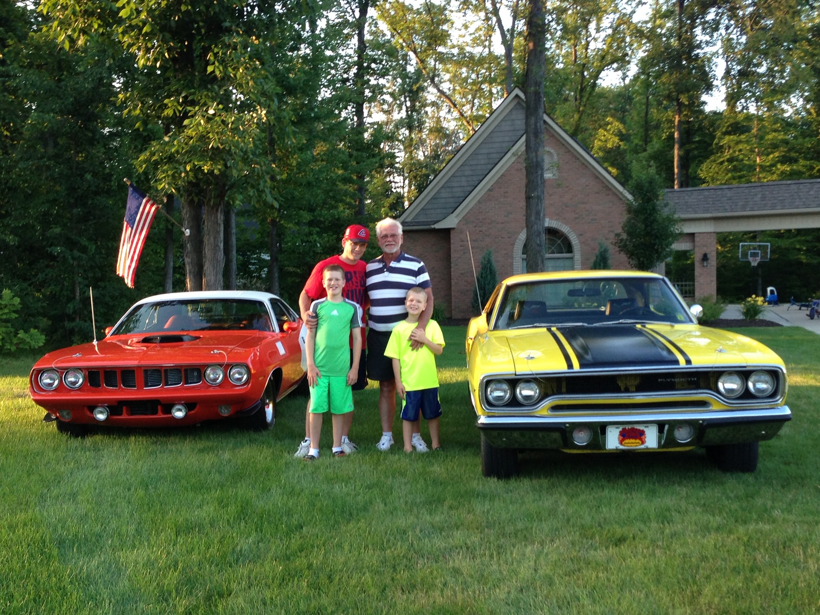 Raymond, Brian, Zachary, Dominic, orange 1971 Plymouth Cuda and   yellow 1970 Plymouth Road Runner with black hood stripes