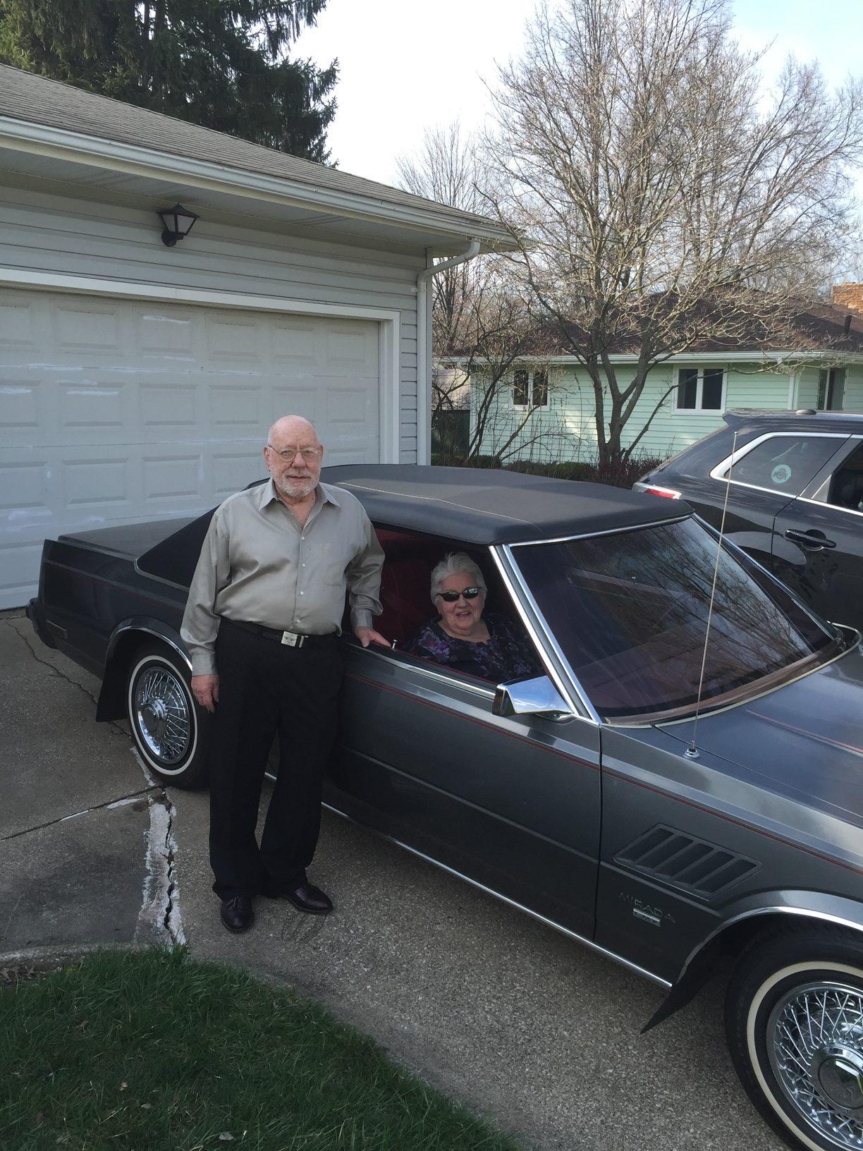Christina's grandparents posing with by the gray 1982 Dodge Mirada CMX