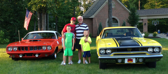 Family posing in front of classic Mopar vehicles
