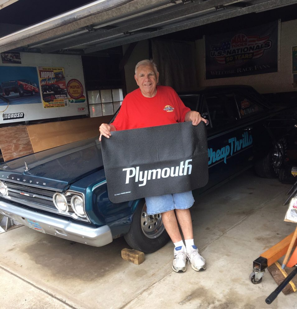 John holding up a Plymouth banner