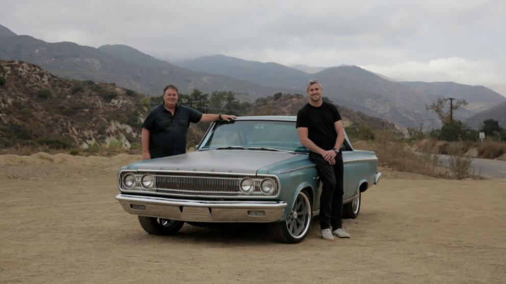 2 men standing beside their 1965 Dodge Coronet