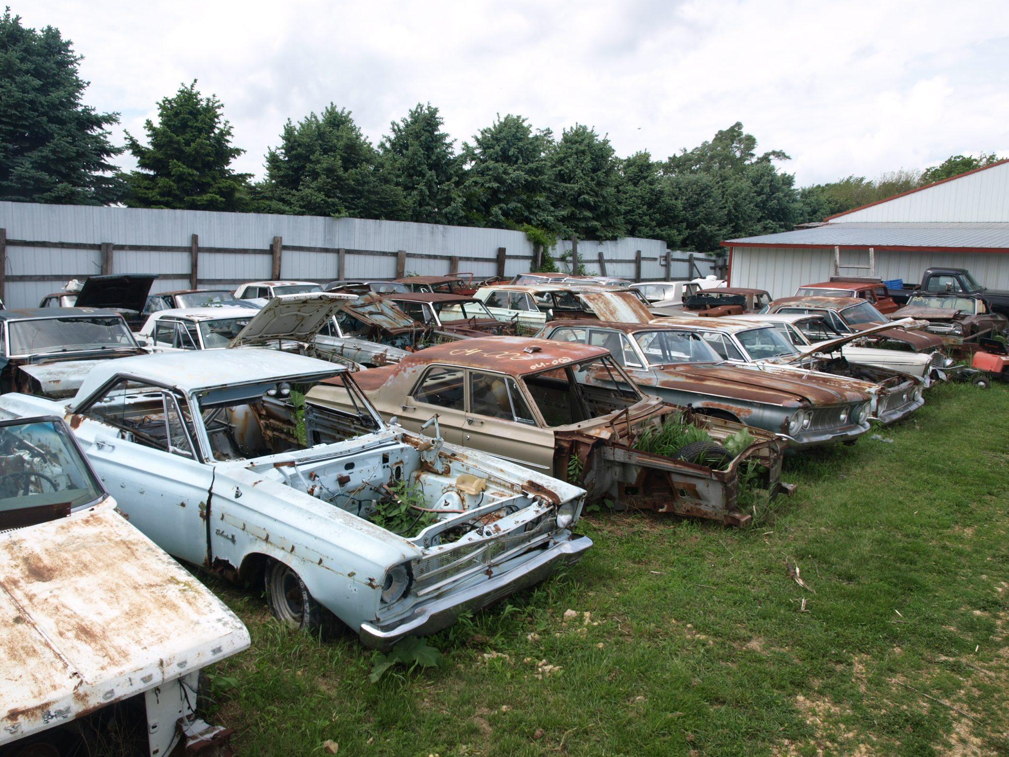 Classic Mopar vehicles sitting in a field at Mopar City