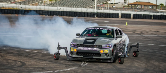 Dodge vehicle with training wheels doing a burnout