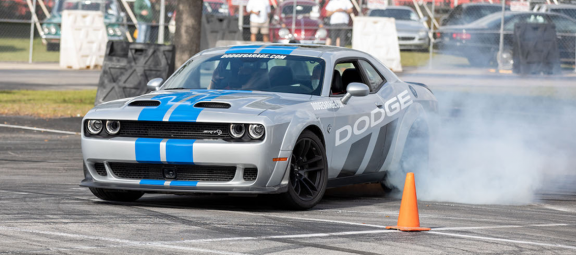 Dodge vehicle drifting around a cone